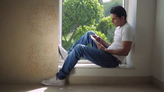 WS Mid-adult man sitting on window sill, using tablet pc / India