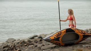 WS PAN Blonde woman in bikini carrying kayak along beach / Singapore