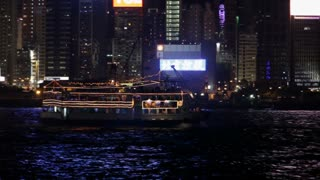 WS PAN Boat floating by on Victoria Harbor with city skyline behind / Hong Kong