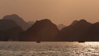 WS PAN Limestone mountains in Ha Long Bay at sunset / Vietnam