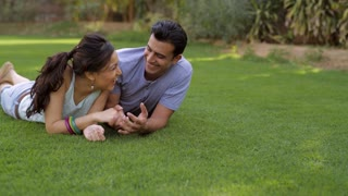 WS PAN Mid-adult couple lying on grass, talking / India