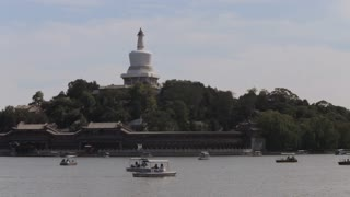WS PAN People swimming in boats on Beihai Park lake with National Grand Theater in background / Beijing, China