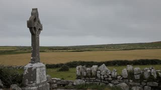 WS PAN Tombstone and Stone Wall with Green Fields in Background / Ireland