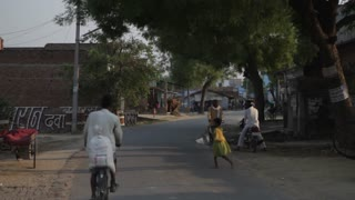 WS People Riding Bikes down Village Road / Saranth, India