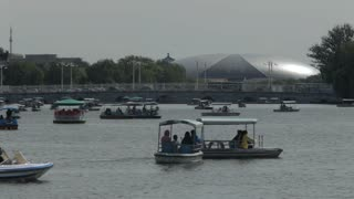 WS People swimming in boats on Beihai Park lake with National Grand Theater in background / Beijing, China
