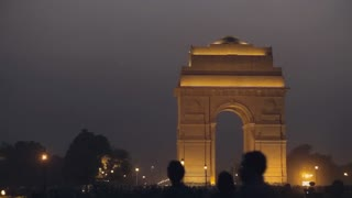 WS People walking past India Gate lit up at night / New Delhi, India