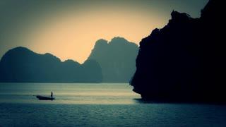WS Person rowing fishing boat in Ha Long Bay / Vietnam