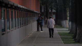 WS Rear view of senior man walking on sidewalk along a wall / Beijing, China