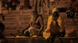 WS Sadhus sitting by river Ganges at night / Varanasi, India