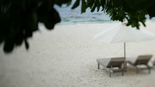 WS SELECTIVE FOCUS Two lounge chairs and white umbrella on isolated beach