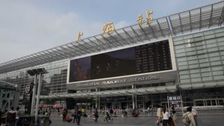 WS Shanghai Railway Station with big screen and people walking in foreground / Shanghai, China