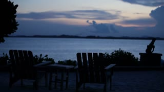 WS Silhouette of deck chairs against ocean skyline / Indonesia