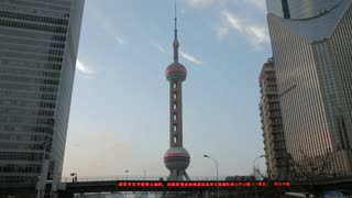 WS The Oriental Pearl Tower with Chinese ticker board in foreground / Shanghai, China