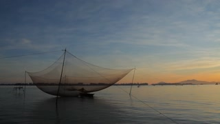 WS Traditional Fishing Net Hoisted Above Water at Sunset / Vietnam