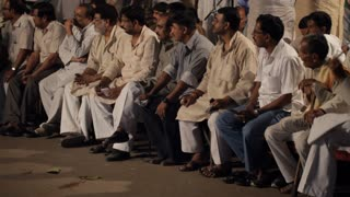 WS TU Men sitting on side of street while another man is speaking on stage / India