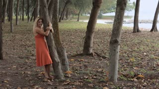 WS TU Young woman hugging tree
