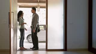 WS Woman adjusting boyfriend's necktie at doorway / India