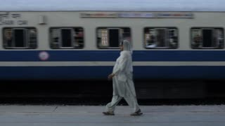 WS Woman walking by moving train / India