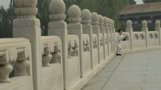 WS Young boy running along stone balustrade / Beijing, China