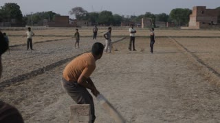 WS Young Boys Playing Cricket in Dirt Field / India