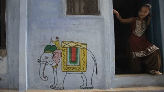 WS Young girl standing in doorway of house with elephant painted on wall / Varanasi, India