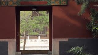 WS Young woman with paper umbrella walking past temple doorway/ Beijing, China