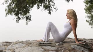Young blonde woman reclining on rocks, side view
