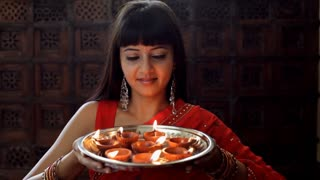 Young Indian woman holding a tray of small oil lamps and smiling.