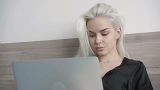 Attractive Beautiful Girl Chat with Friend on Laptop in bed at Morning