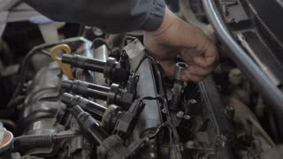 Auto Mechanic is Working on Engine in Car Repair Shop