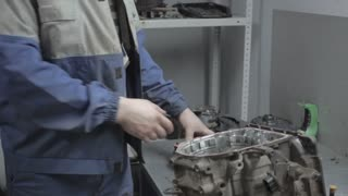 Auto Mechanic Repairing a Car Engine and Macro View of Automatic Robot Transmission