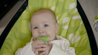 Baby Child Lying on Seat weared with Teether in Mouth