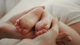 Baby Feet in Mother Hands. Tiny Newborn Baby's Feet on Female Heart Shaped Hands Closeup. Mom and her Child. Happy Family concept.