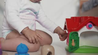 baby girl playing with educational toy in nursery. Logic child game