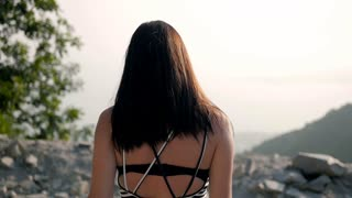 Back View of Young Brunette Going To The Edge of The Mountains
