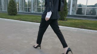 Back View of Young Business Woman Legs In High-Heeled Shoes Walking Outdoors