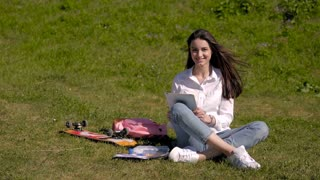 Beautiful Happy Smiling Brunette Using Tablet PC Sitting In Park On a Sunny Day