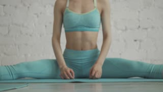 Beautiful Young Woman Doing Yoga Workout In a Stretching Class