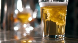 Beer into glass with a lot of bubles and foam super close up slow motion