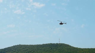 Black Helicopter Hovers And Flies In Air Against Blue Ssky With Mountains In Background