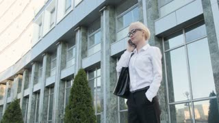 Business Woman Making a Phone Call Outside Business Center