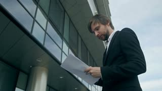 Businessman at work outside the office. Confident and successful businessman holding a tablet and stands near the business center