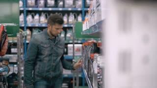 Car mechanic man choose motor oil for car at repair service station supermarket. A lot of goods for trucks