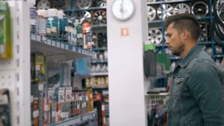 Car mechanic man choose motor oil for car at repair service station supermarket. A lot of goods for trucks