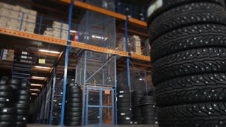 Car Tires At Warehouse In Tire Store. A Huge Warehouse of a Car Tires With Elevator