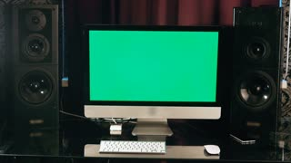 Chroma key. Stylish workspace with computer green screen and audio dinamics on home or studio