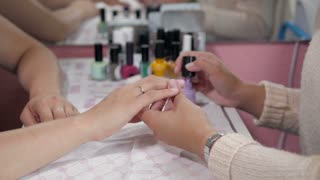 Closeup shot of a woman in a nail salon receiving a manicure by a beautician with nail file. Woman getting nail manicure. Beautician file nails to a customer. Blurred background