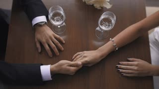 Closeup Toned  of Bride and Groom Holding Hands at Restaurant