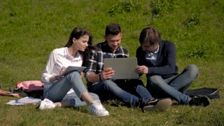 College Students Using Laptop And Tablet On Campus Lawn, Outdoor Study Concept