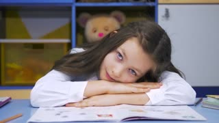 Cute little Girl Studying at the Library Doing Homework and Smiling. Elementary school. Child reading